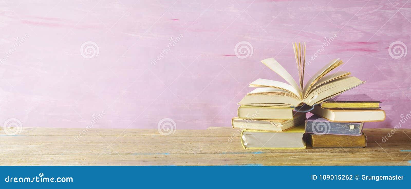 Ανοικτό βιβλίο σε έναν σωρό των βιβλίων,