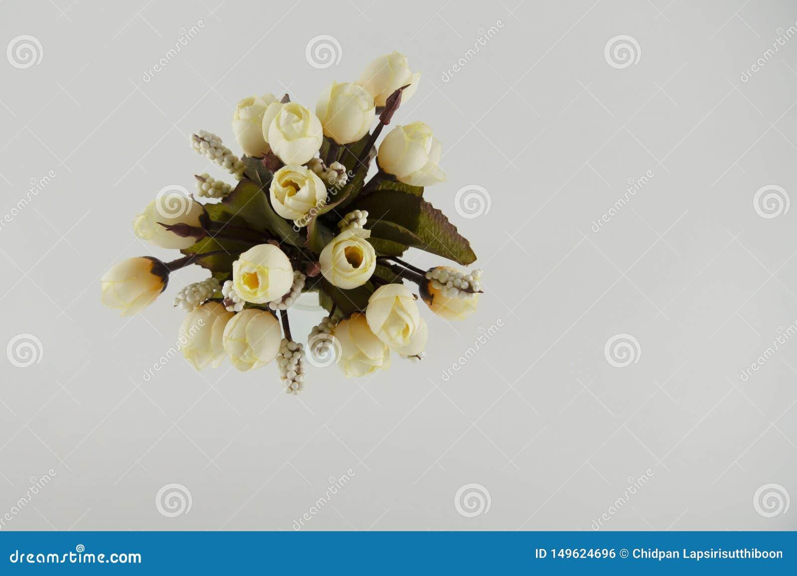 Ανοικτό κίτρινο πλαστικά λουλούδια σε ένα βάζο γυαλιού