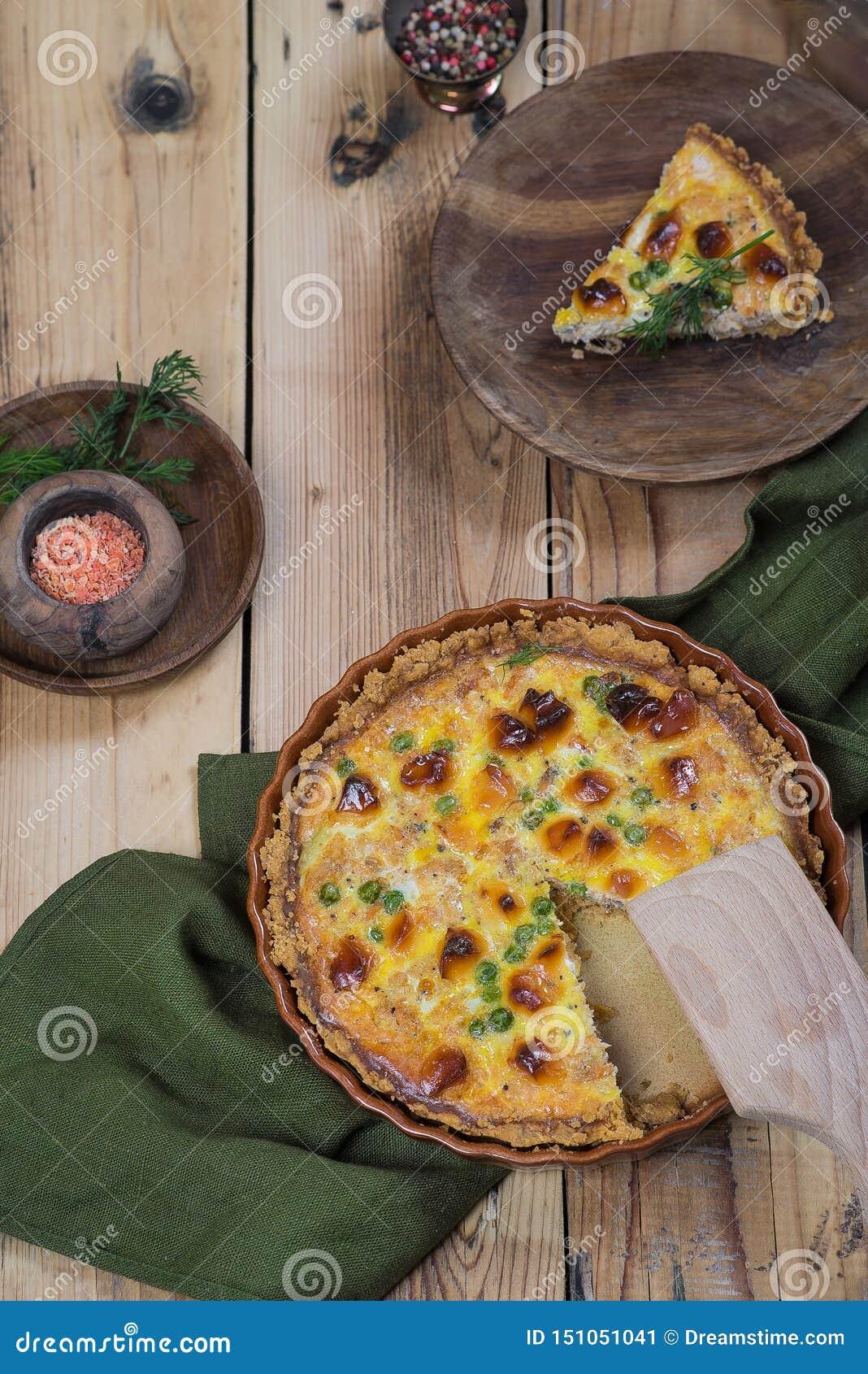 Ανοικτό στρογγυλό κέικ με το τυρί και πράσινα μπιζέλια σε ένα ξύλινο υπόβαθρο