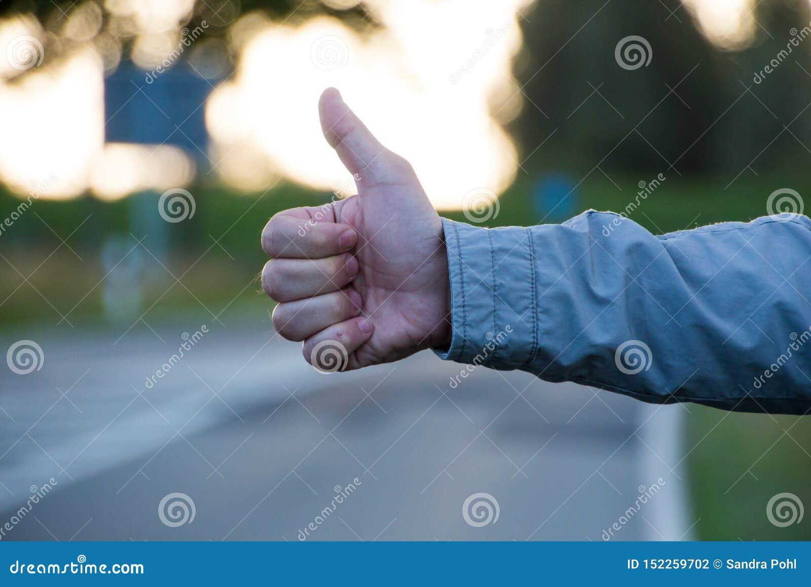 Αντίχειρας επάνω σε έναν δρόμο κάνοντας ωτοστόπ