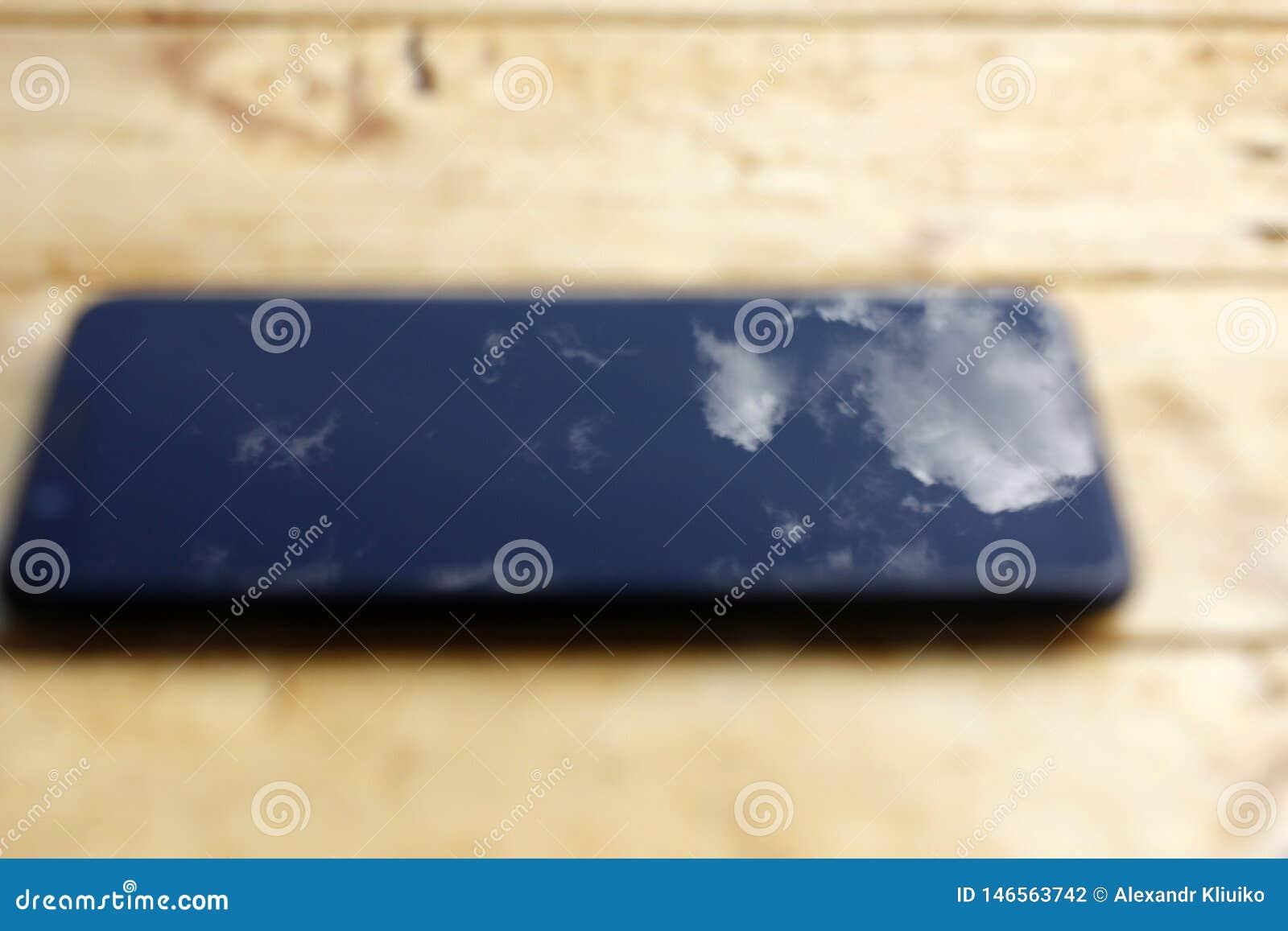 Αντανάκλαση του μπλε ουρανού με τα άσπρα σύννεφα στην οθόνη smartphone σε ένα ξύλινο υπόβαθρο στη θαμπάδα