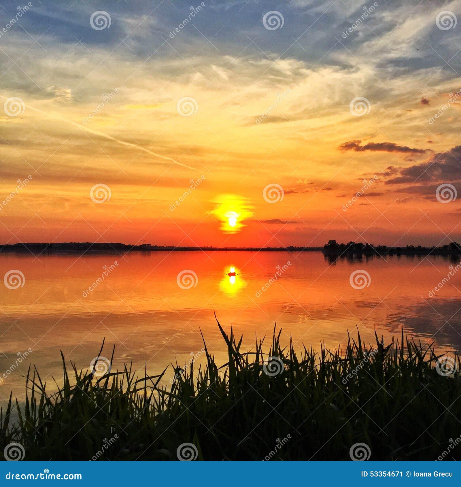 Αντανάκλαση ηλιοβασιλέματος στην ήρεμη λίμνη