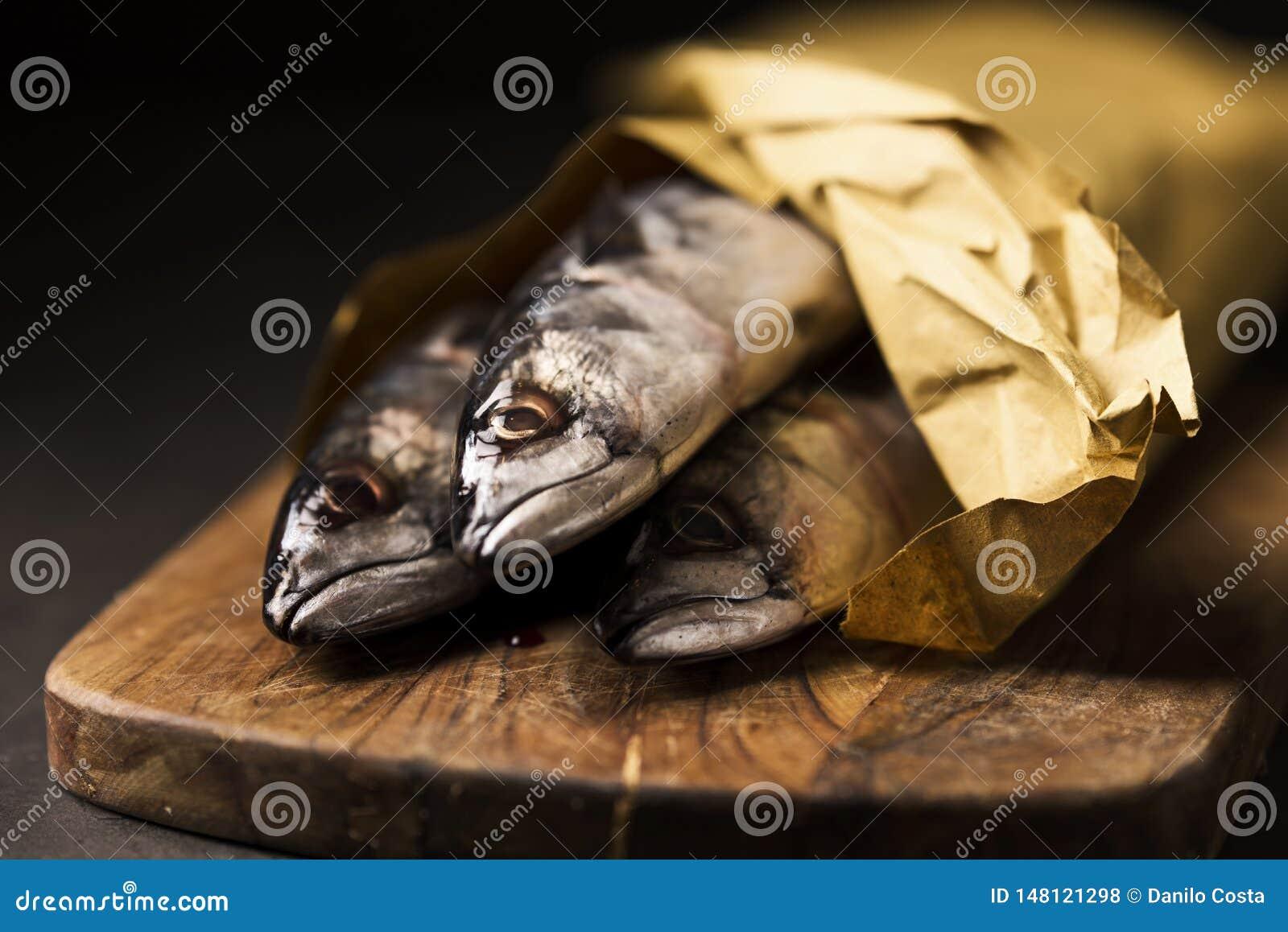 Αντσούγιες ψαριών σκουμπριών στον ξύλινους τέμνοντες πίνακα και το πιάτο