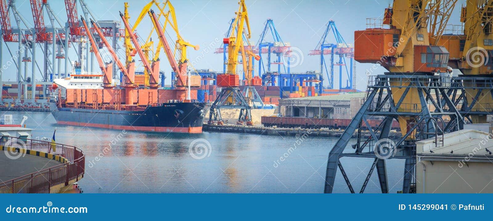 Ανυψωτικοί γερανοί φορτίου, σκάφη και στεγνωτήρας σιταριού στο θαλάσσιο λιμένα