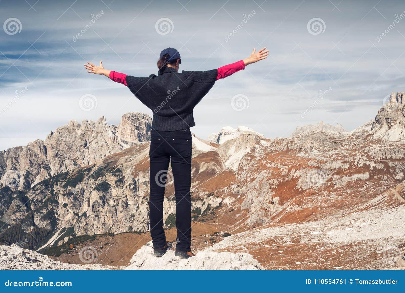 Ανώνυμος θηλυκός οδοιπόρος μπροστά από ένα όμορφο τοπίο βουνών αιχμές τρία δολομίτες Ιταλία
