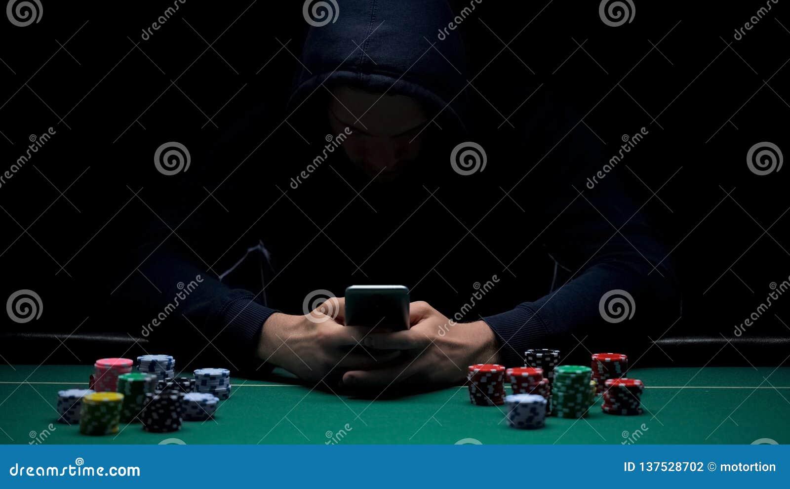 Ανώνυμο αρσενικό παίζοντας παιχνίδι online στο smartphone app, παράνομη επιχείρηση, εξαρτημένος