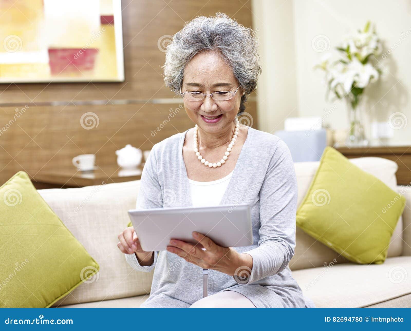 Ανώτερη ασιατική γυναίκα που χρησιμοποιεί τον υπολογιστή ταμπλετών
