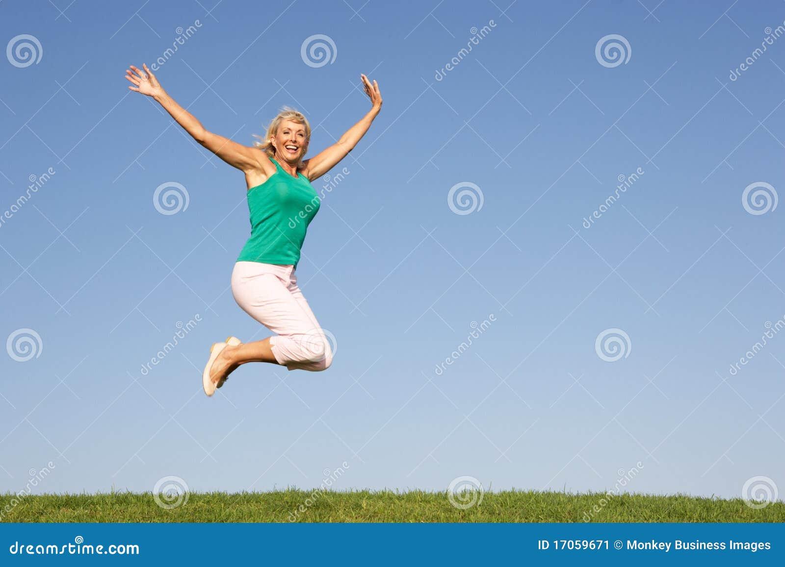 Ανώτερη γυναίκα που πηδά στον αέρα