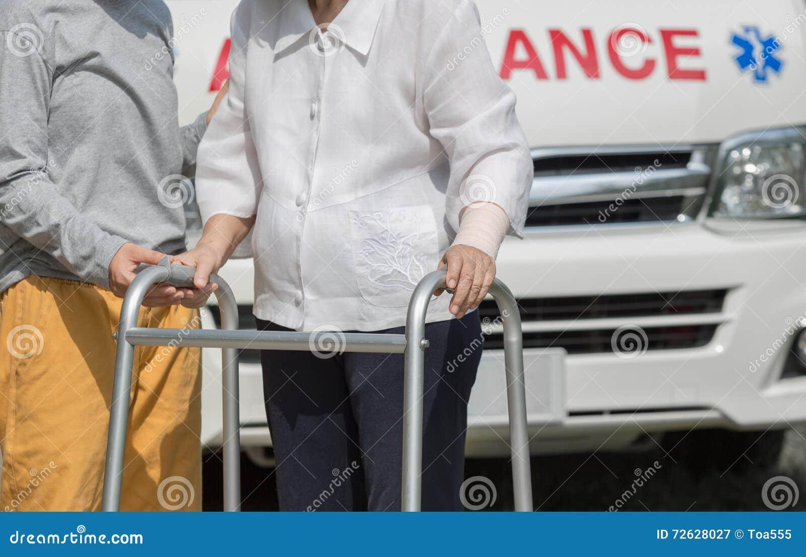 Ανώτερη γυναίκα που χρησιμοποιεί έναν περιπατητή με το caregiver