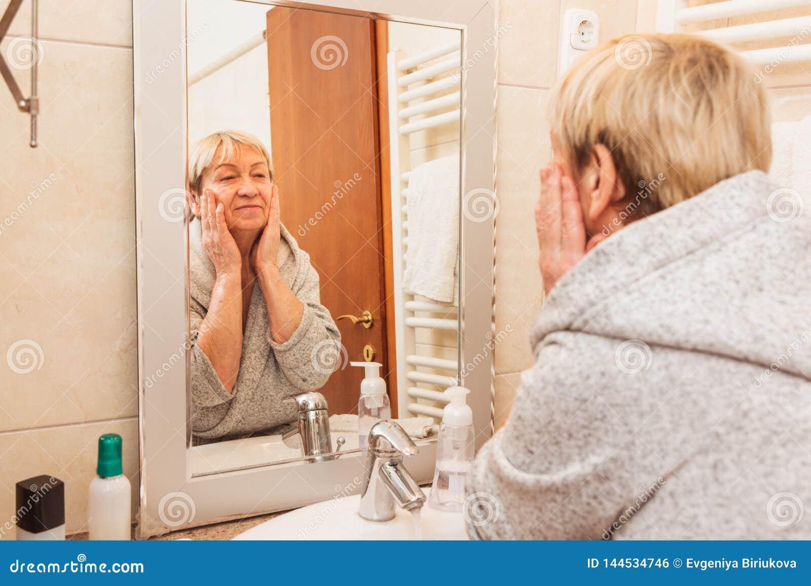 Ανώτερη γυναίκα σχετικά με το μαλακό δέρμα προσώπου της, που κοιτάζει στον καθρέφτη στο σπίτι