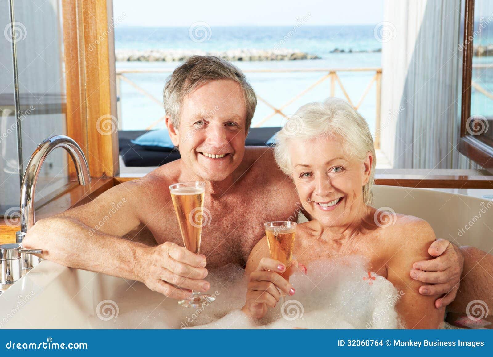 Ανώτερη χαλάρωση ζεύγους στο λουτρό που πίνει CHAMPAGNE από κοινού