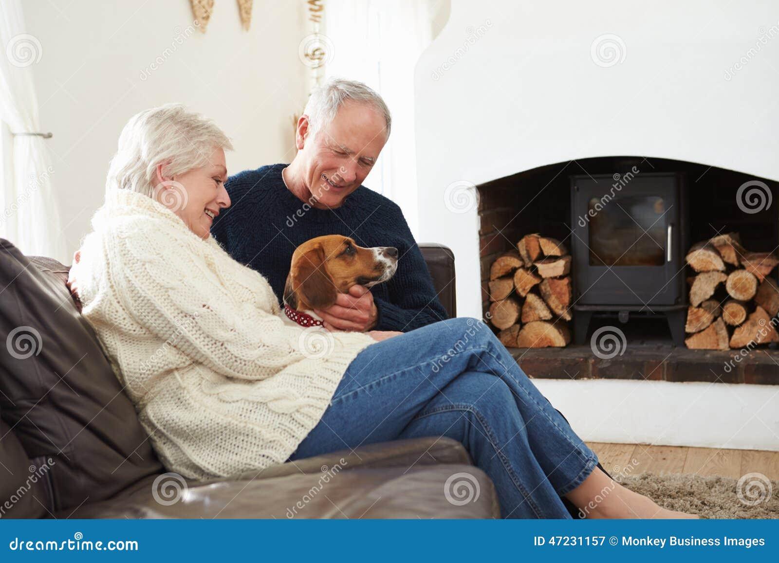 Ανώτερη χαλάρωση ζεύγους στο σπίτι με το σκυλί της Pet