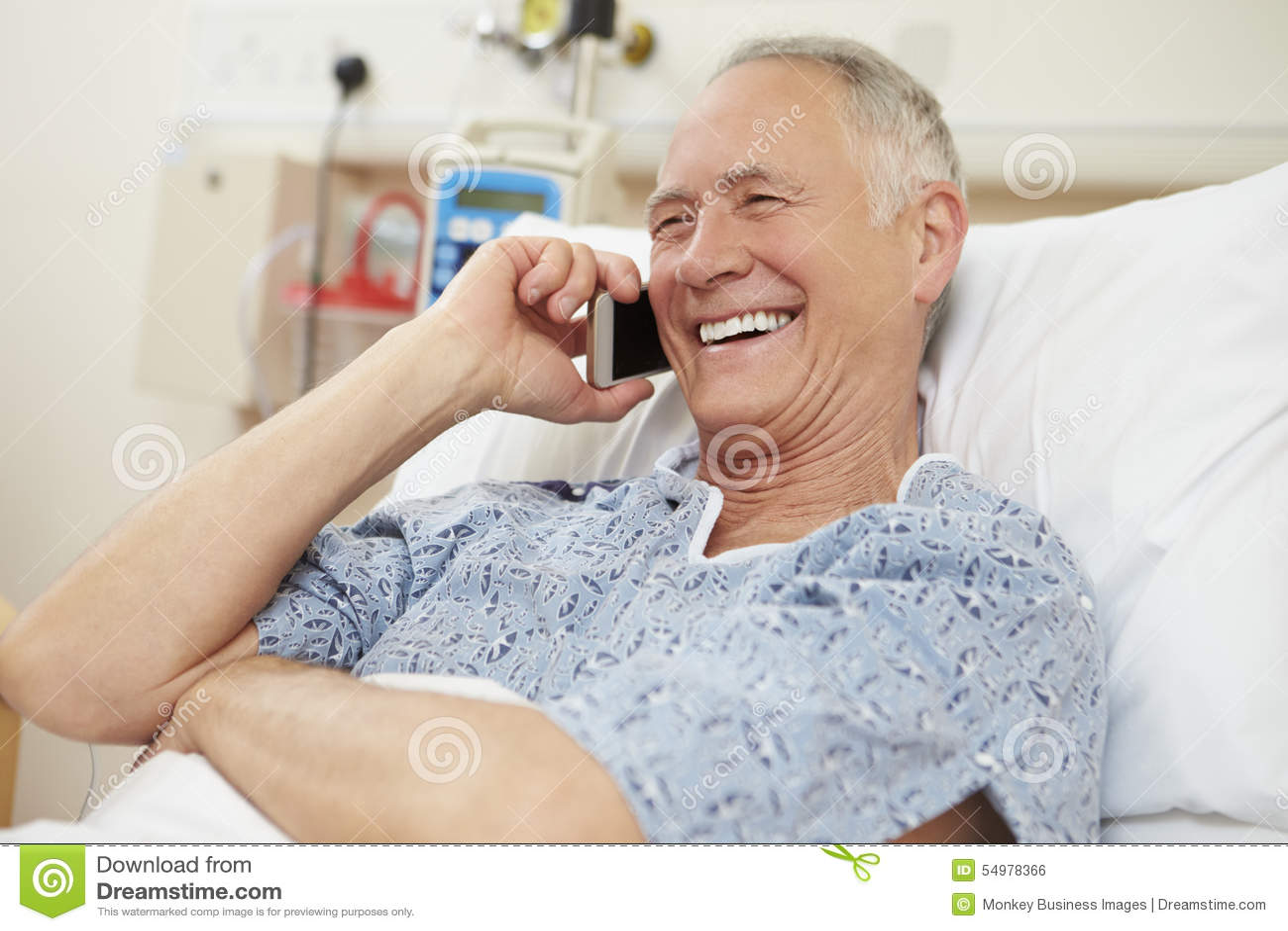 Ανώτερος αρσενικός ασθενής που χρησιμοποιεί το κινητό τηλέφωνο στο νοσοκομειακό κρεβάτι