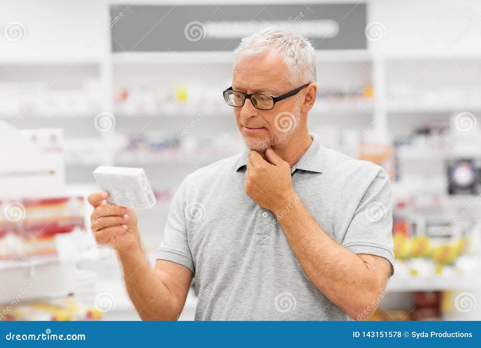 Ανώτερος αρσενικός πελάτης με το φάρμακο στο φαρμακείο