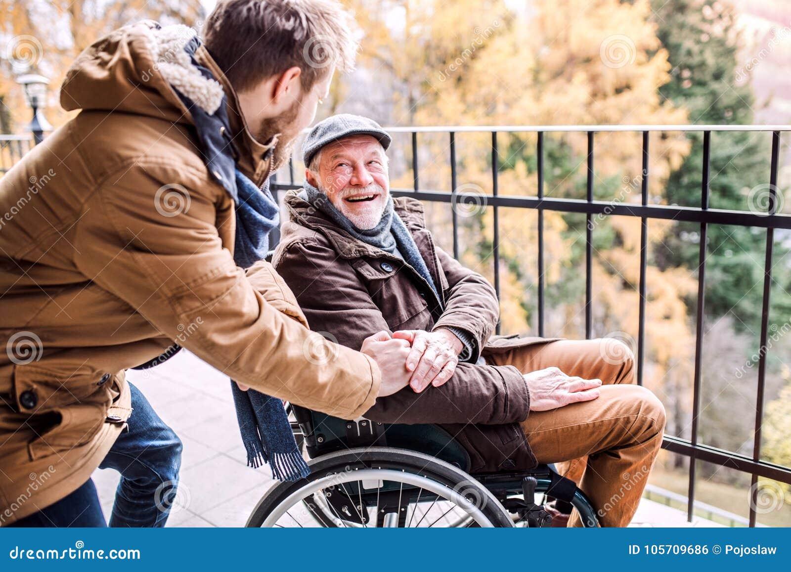Ανώτερος πατέρας στην αναπηρική καρέκλα και νέος γιος σε έναν περίπατο