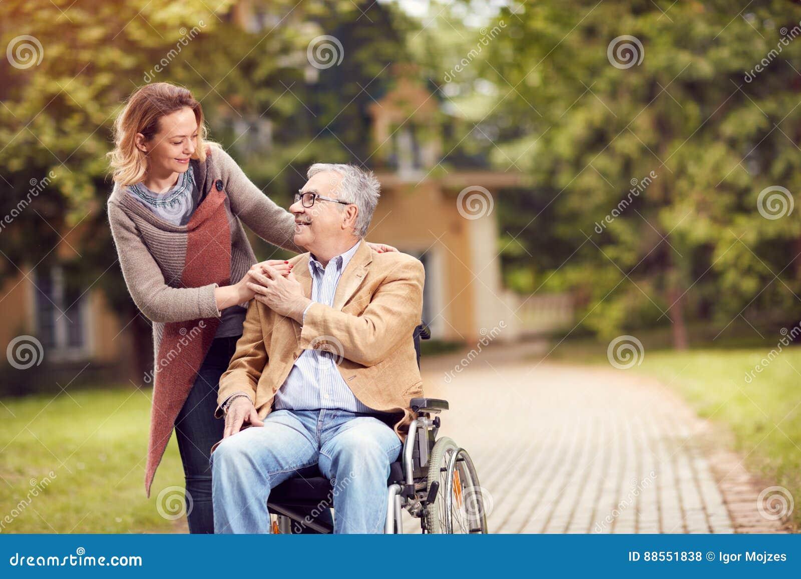 Ανώτερο άτομο στην αναπηρική καρέκλα με την κόρη caregiver