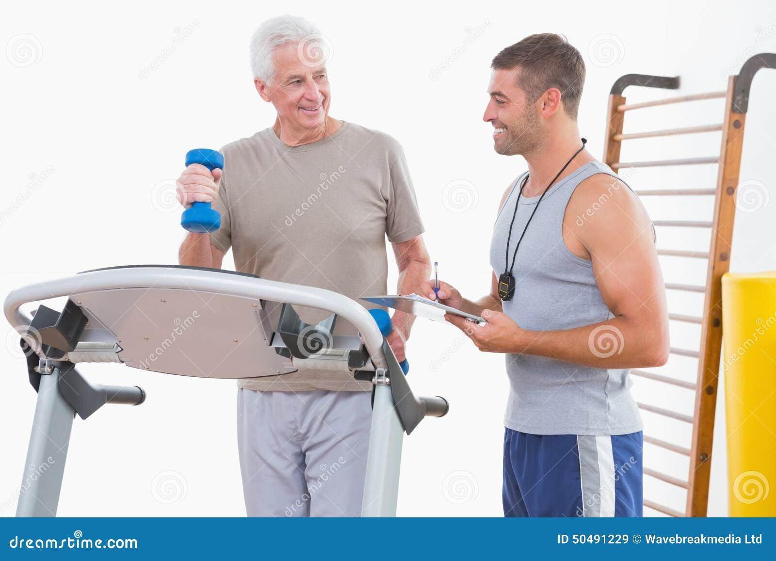 Ανώτερο άτομο treadmill με τον εκπαιδευτή