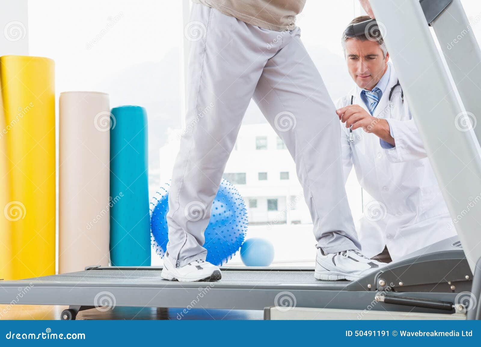 Ανώτερο άτομο treadmill με το σκύψιμο θεραπόντων