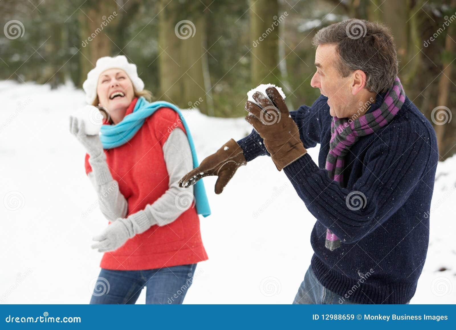 Ανώτερο ζεύγος που έχει την πάλη χιονιών στο χιόνι