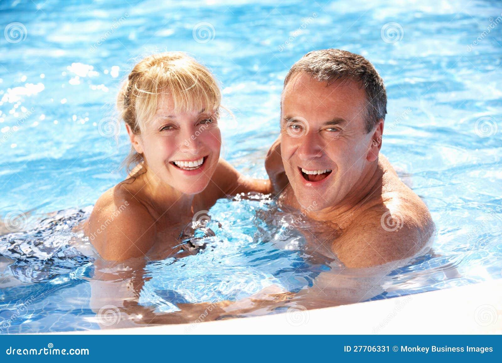 Ανώτερο ζεύγος που έχει τη διασκέδαση στην πισίνα