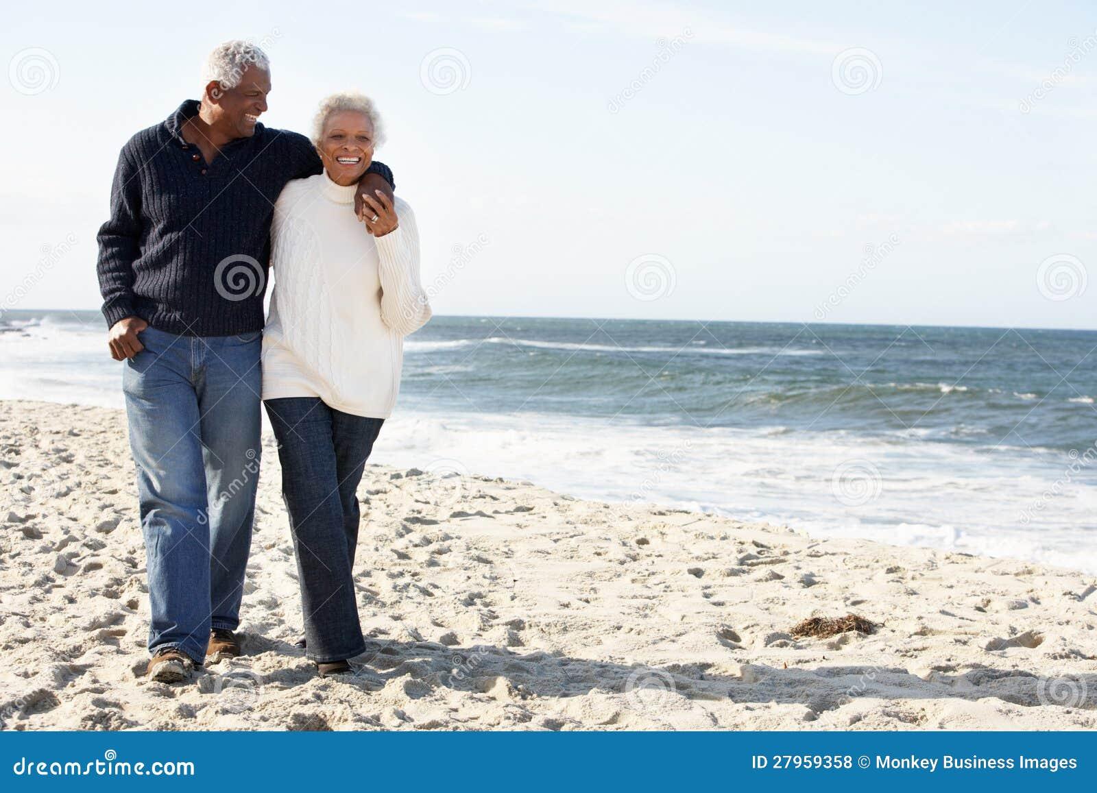 Ανώτερο ζεύγος που περπατά κατά μήκος της παραλίας από κοινού