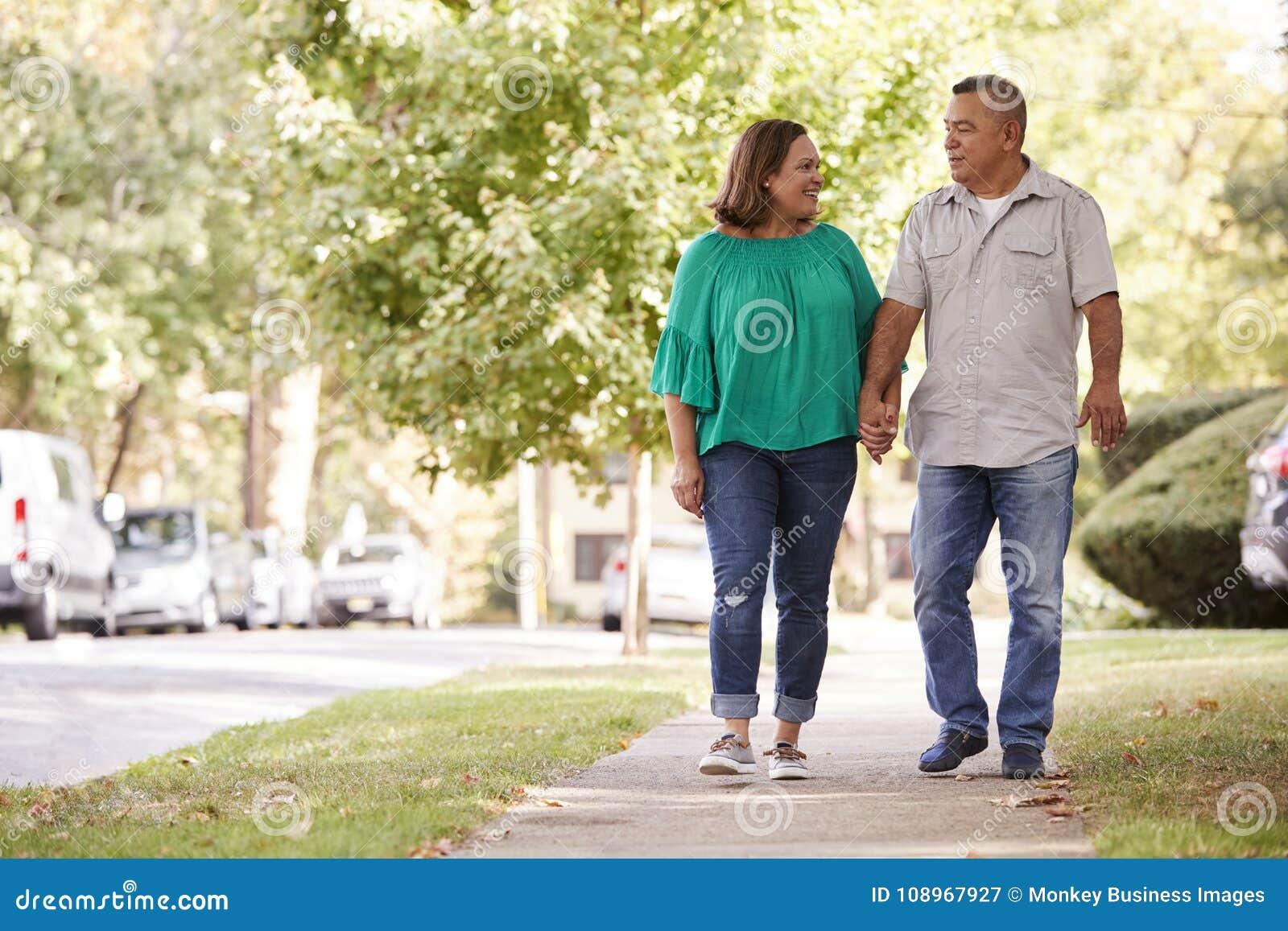 Ανώτερο ζεύγος που περπατά κατά μήκος των προαστιακών χεριών εκμετάλλευσης οδών