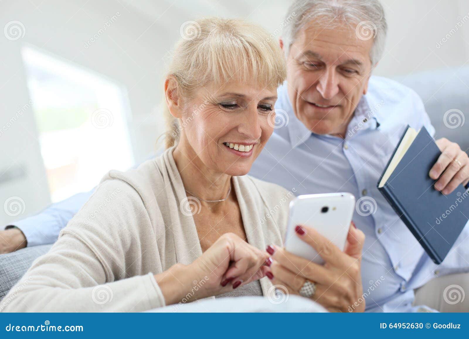 Ανώτερο ζεύγος που χρησιμοποιεί το smartphone στο σπίτι