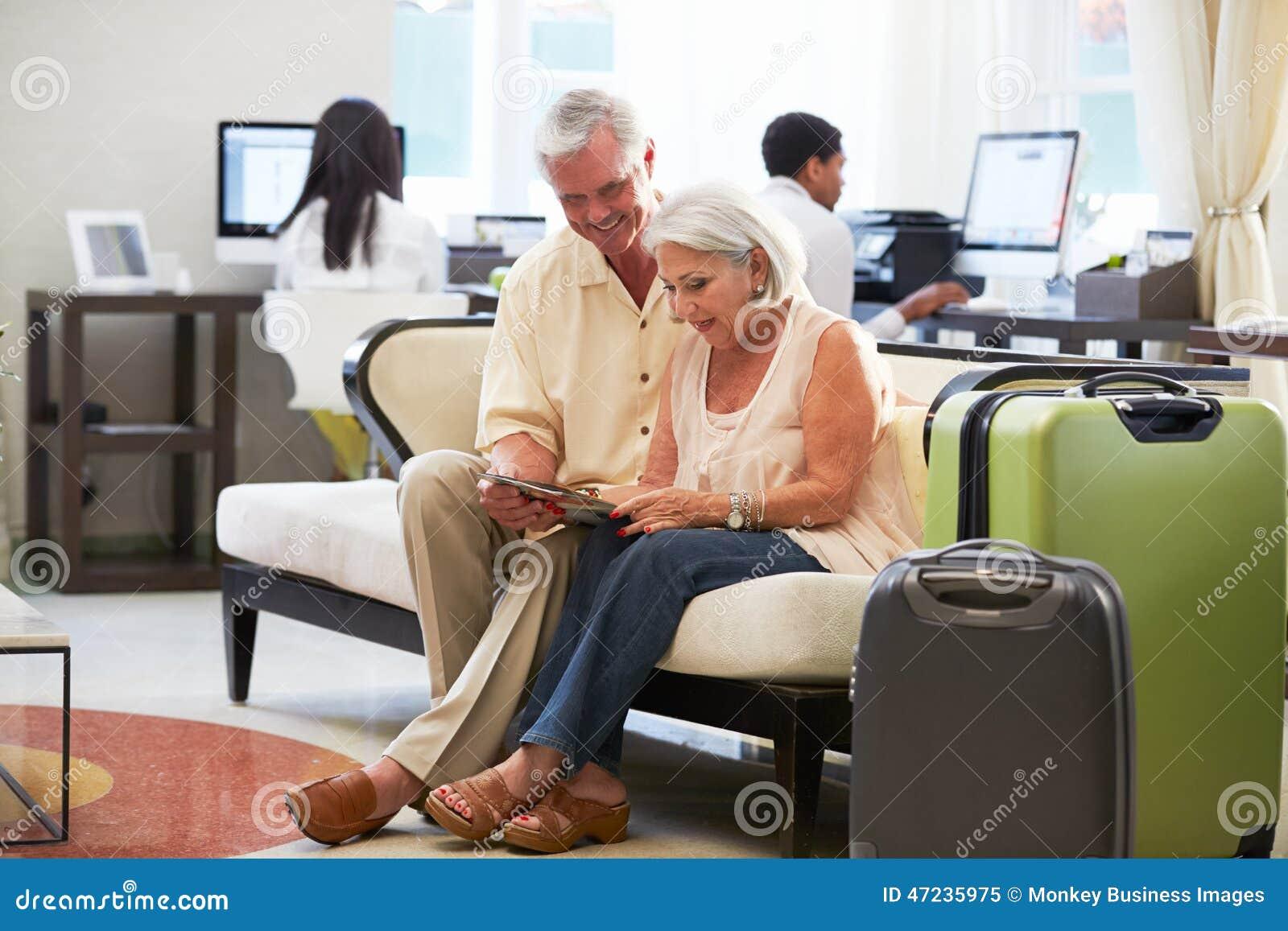 Ανώτερο ζεύγος στο λόμπι ξενοδοχείων που εξετάζει την ψηφιακή ταμπλέτα