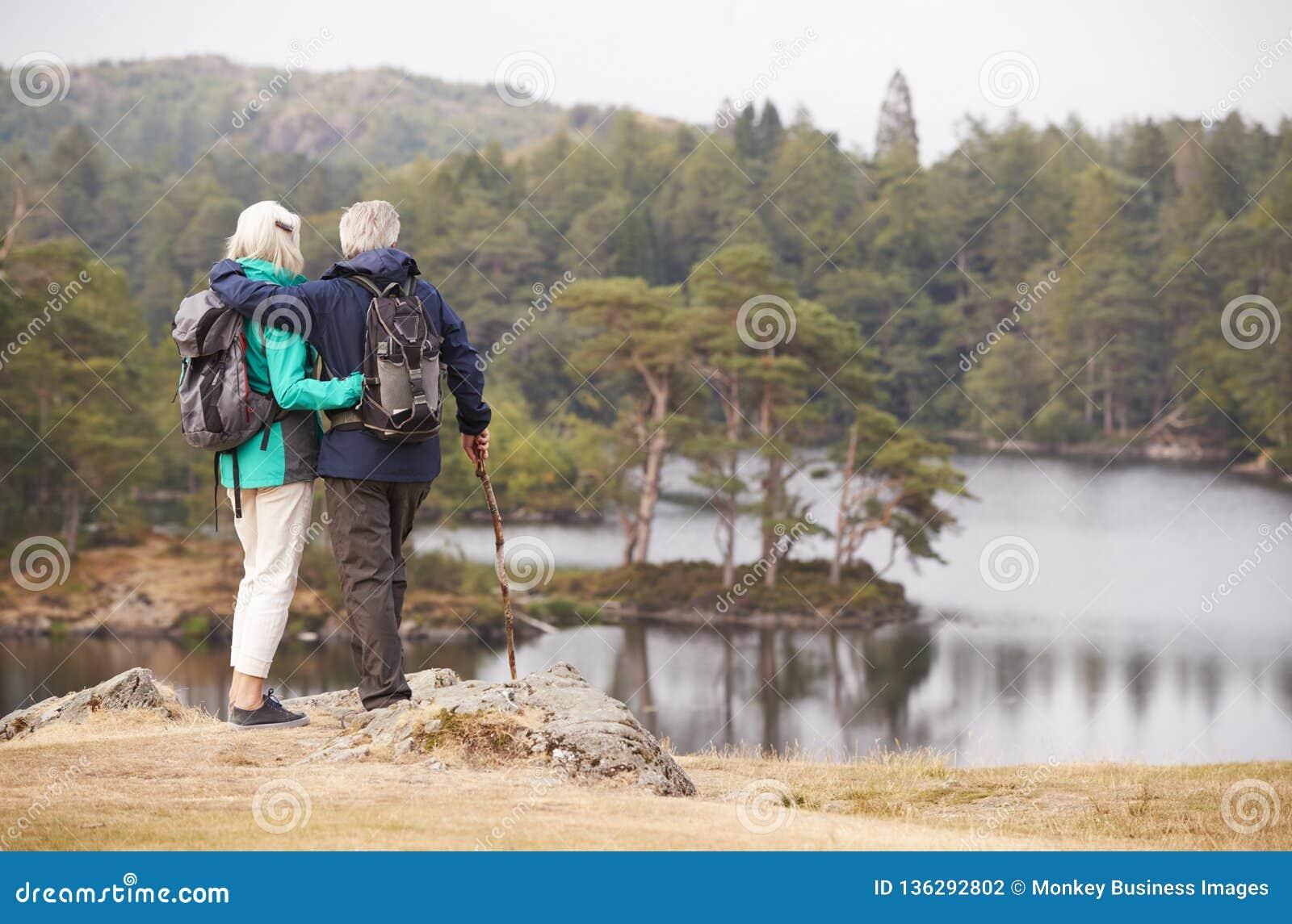 Ανώτερο μόνιμο αγκάλιασμα ζευγών και θαυμασμός της άποψης μιας λίμνης, πίσω άποψη