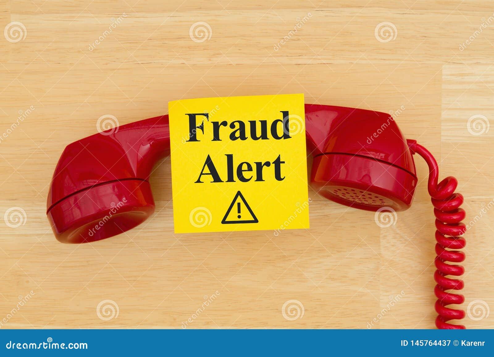 Απάτη άγρυπνη στην κολλώδη σημείωση με ένα αναδρομικό κόκκινο τηλέφωνο στο κατασκευασμένο ξύλινο γραφείο