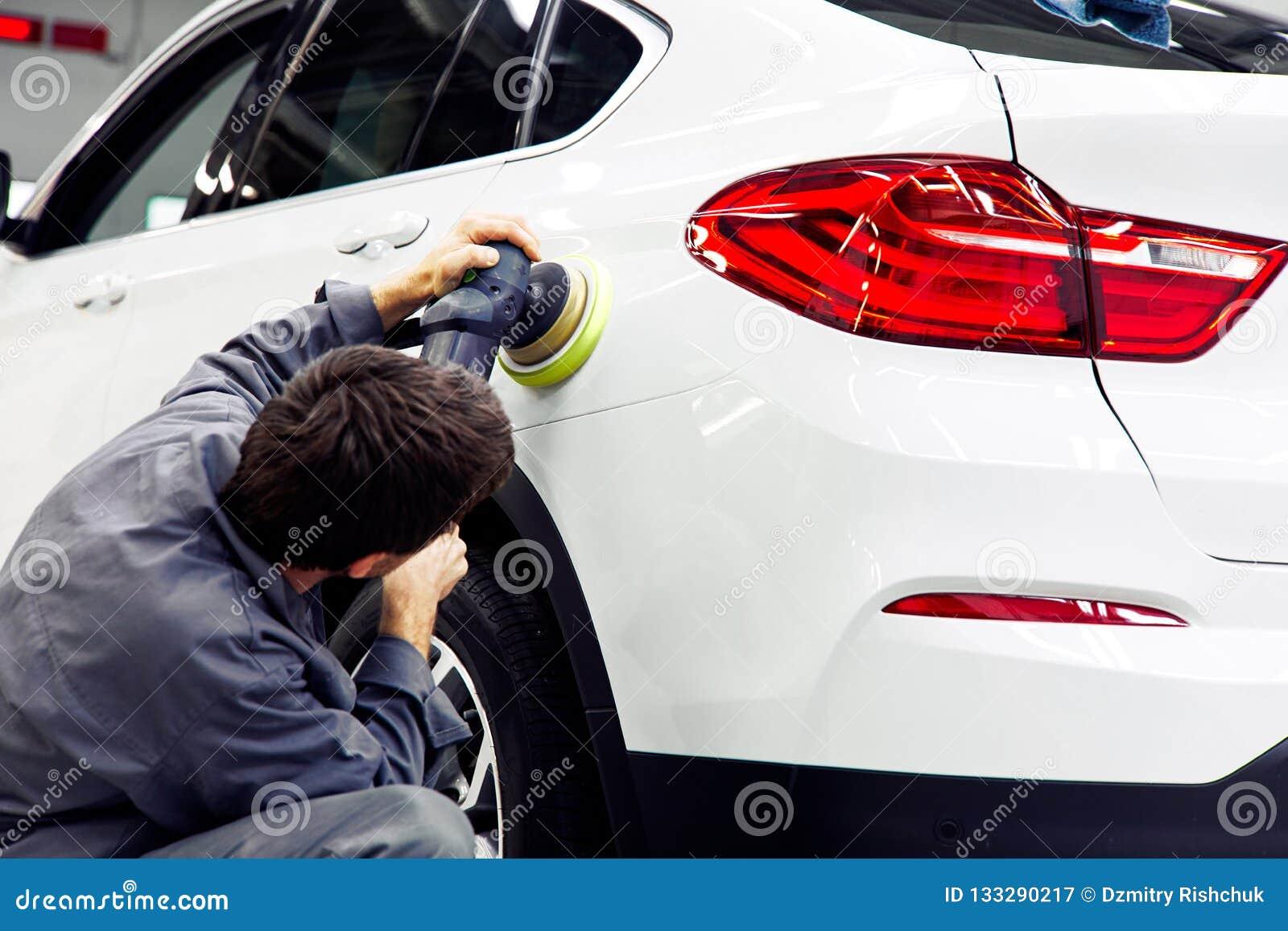 Απαρίθμηση αυτοκινήτων - χέρια με τον τροχιακό στιλβωτή στο αυτόματο κατάστημα επισκευής