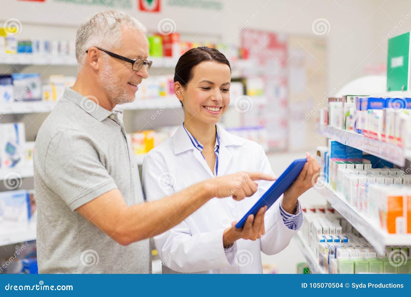 Αποθηκάριος και πελάτης με το PC ταμπλετών στο φαρμακείο