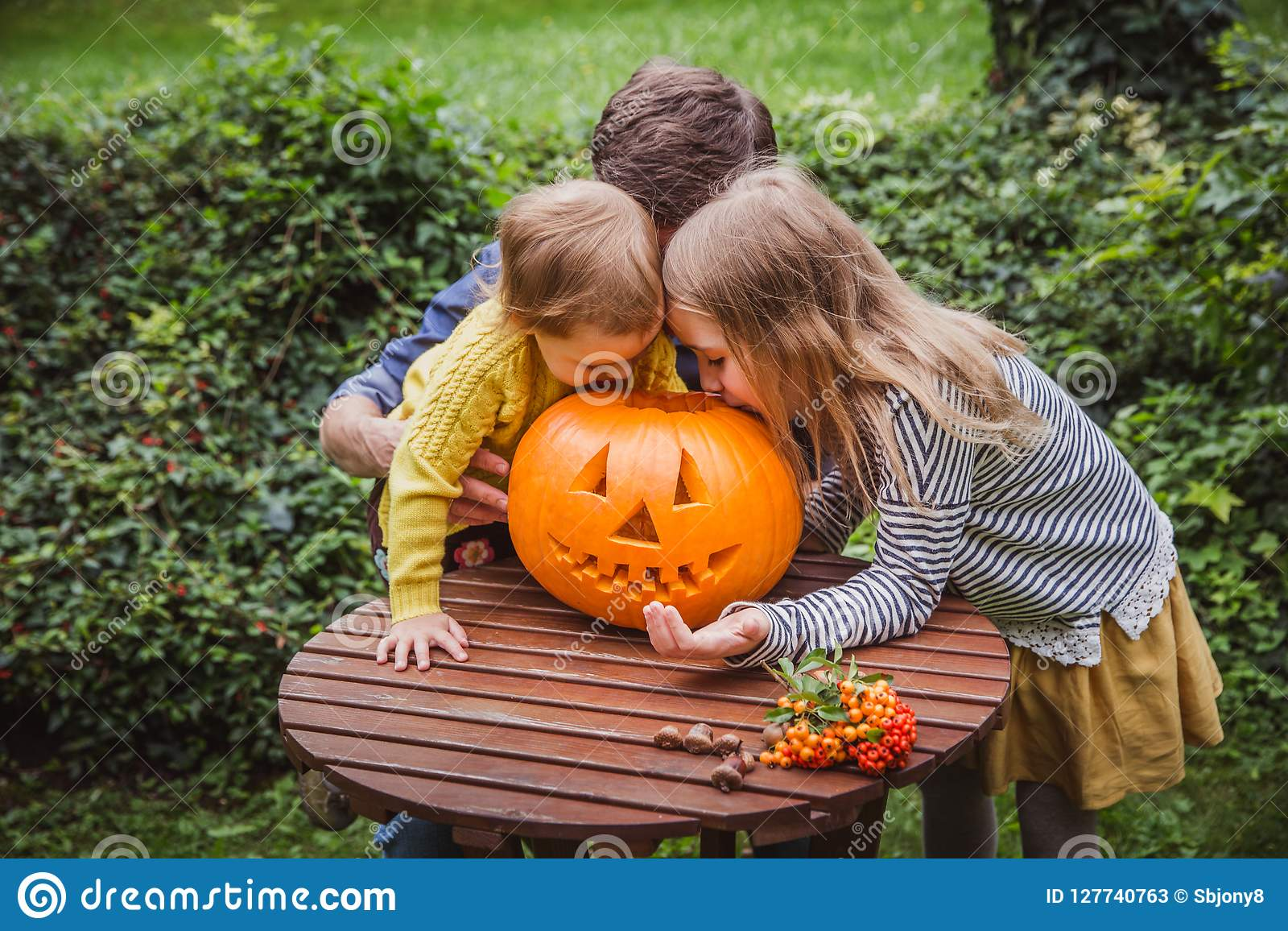 αποκριές ευτυχείς Πατέρας και δύο κόρες κοιτάζουν μέσα στη χαρασμένη κολοκύθα για αποκριές έξω