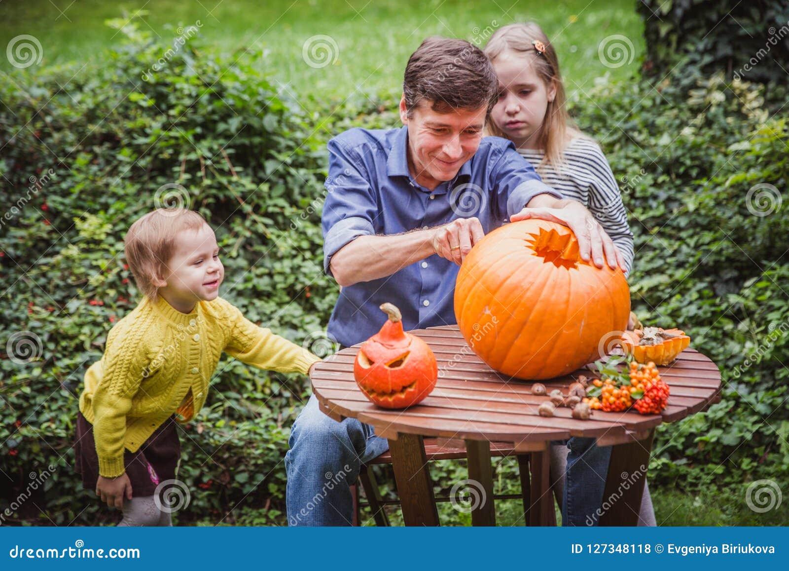 αποκριές ευτυχείς Χαράζοντας κολοκύθα πατέρων και δύο κορών για αποκριές έξω οικογένεια ευτυχής