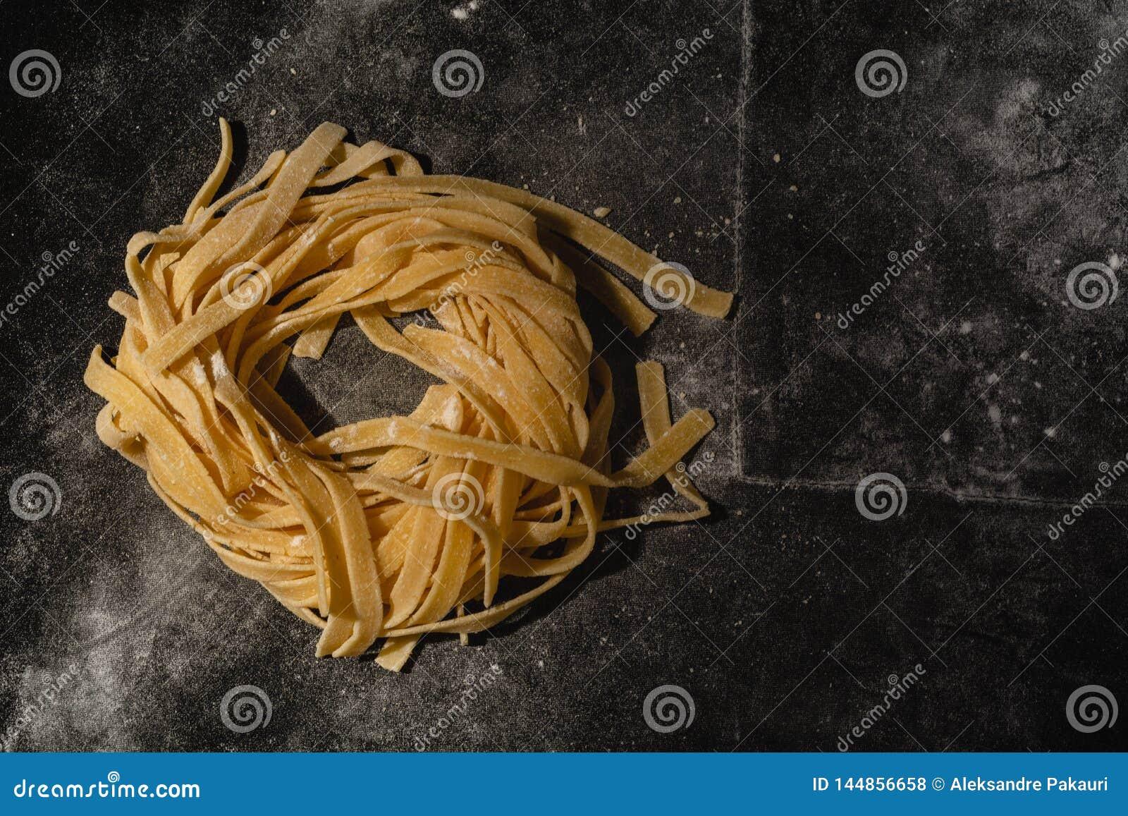 Απομονωμένα ακατέργαστα ζυμαρικά σε ένα μαύρο υπόβαθρο με μια θέση για το κείμενο Παραδοσιακά ιταλικά ζυμαρικά, νουντλς, tagliate