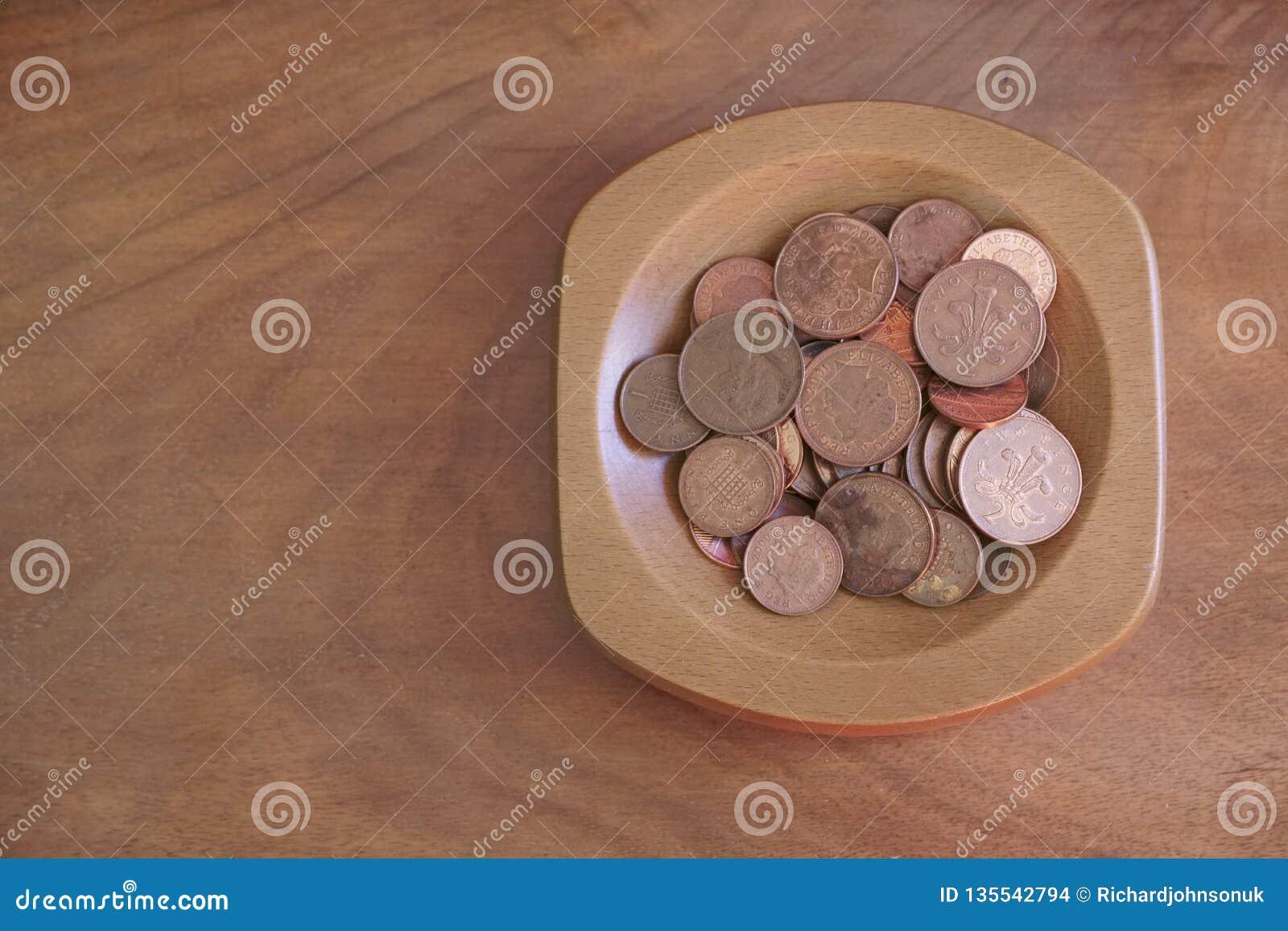 Αποταμίευση πενών χαλκού νομισμάτων συλλογής στο ξύλινο κύπελλο