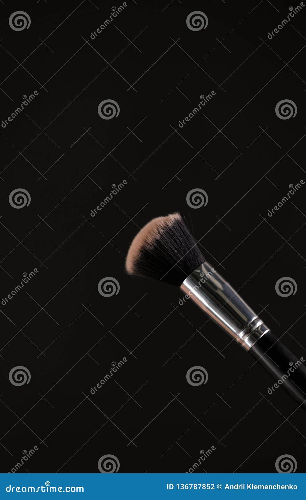 Αποτελέστε τις καλλυντικές βούρτσες με τη σκόνη να κοκκινίσουν έκρηξη στο μαύρο υπόβαθρο