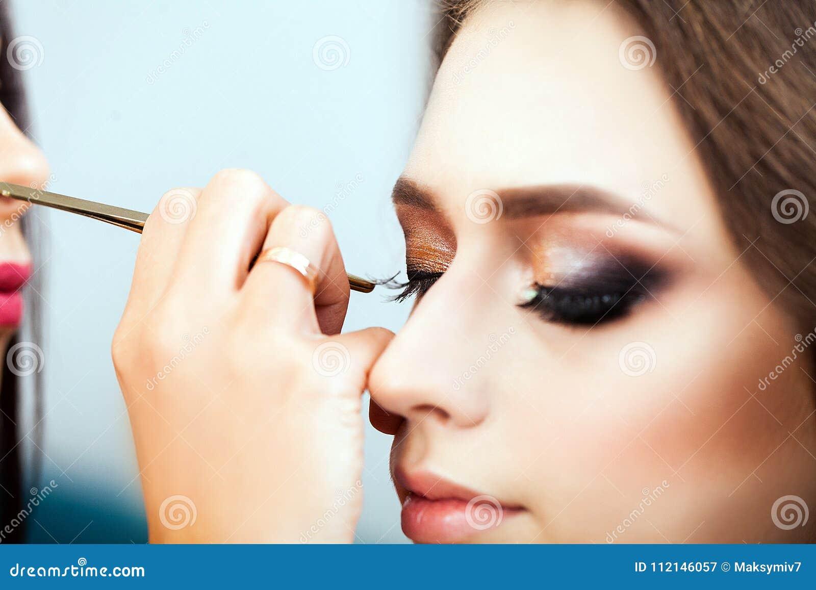 Αποτελέστε τον καλλιτέχνη που εφαρμόζει τη σκιά ματιών σε μια γυναίκα