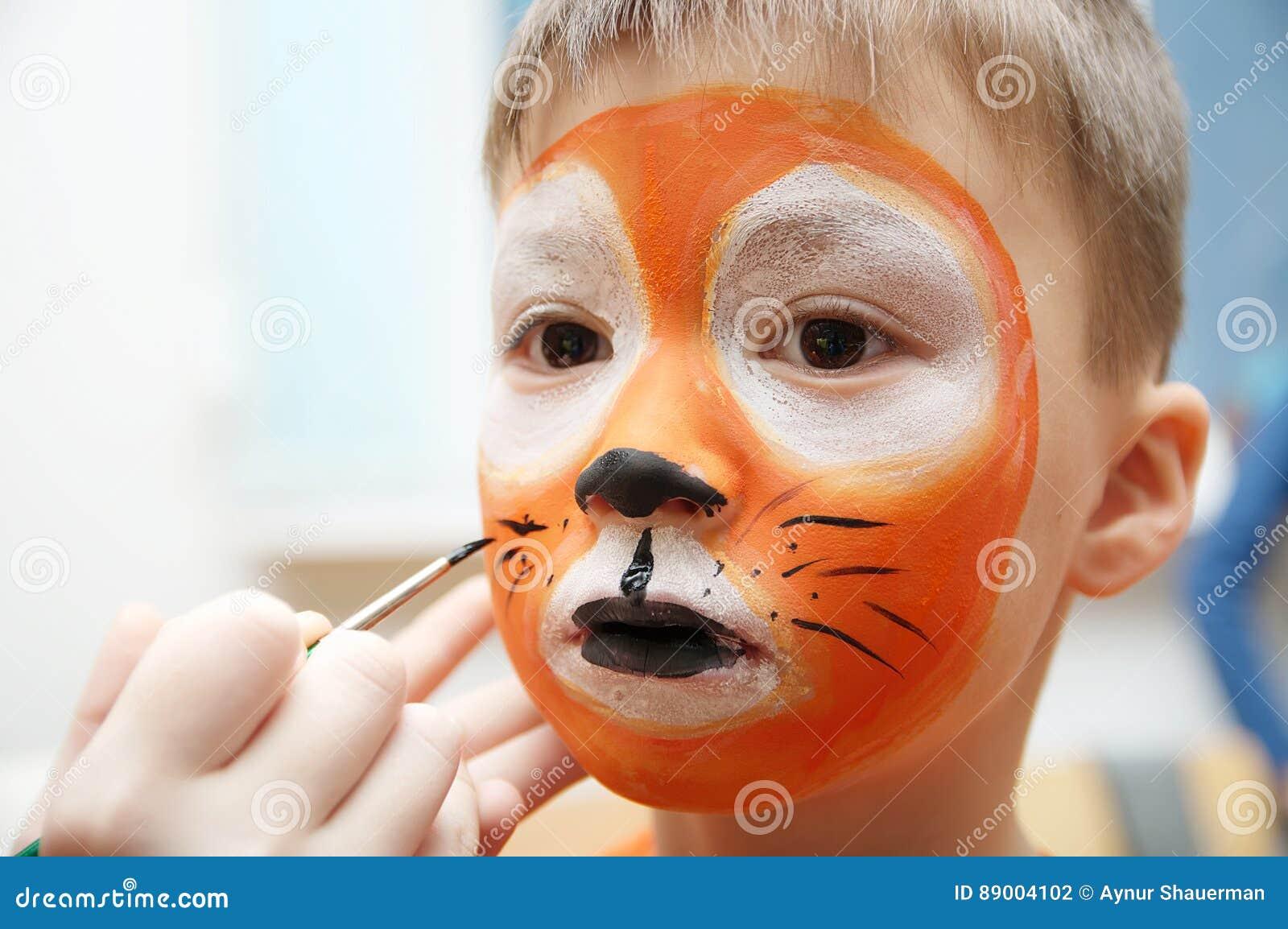 Αποτελέστε τον καλλιτέχνη που κάνει τη μάσκα τιγρών για το παιδί Τα παιδιά αντιμετωπίζουν τη ζωγραφική Το αγόρι χρωμάτισε ως τίγρ