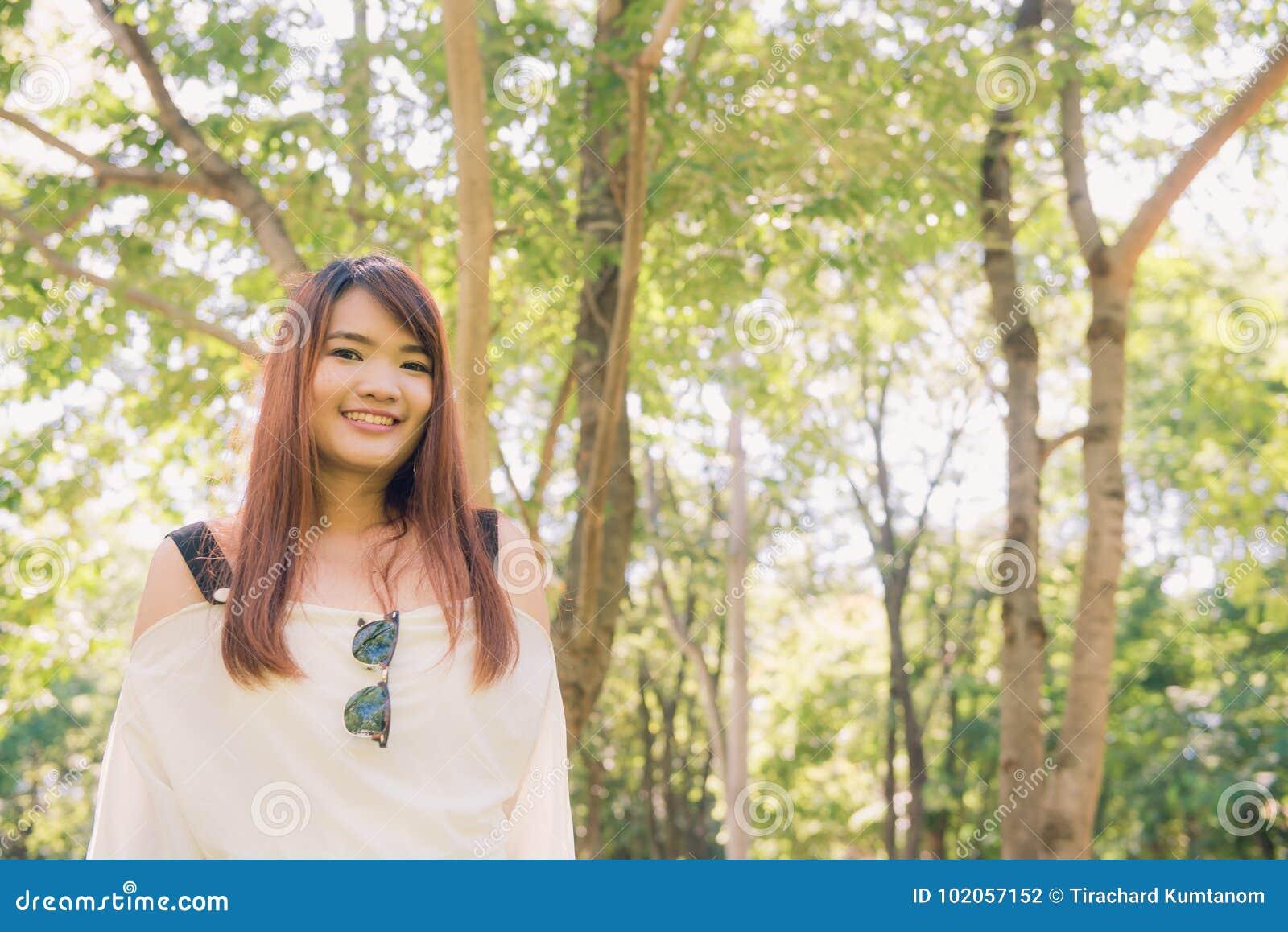 απόλαυση της φύσης Η νέα ασιατική γυναίκα οπλίζει αυξημένος απολαμβάνοντας το καθαρό αέρα στο πράσινο δάσος