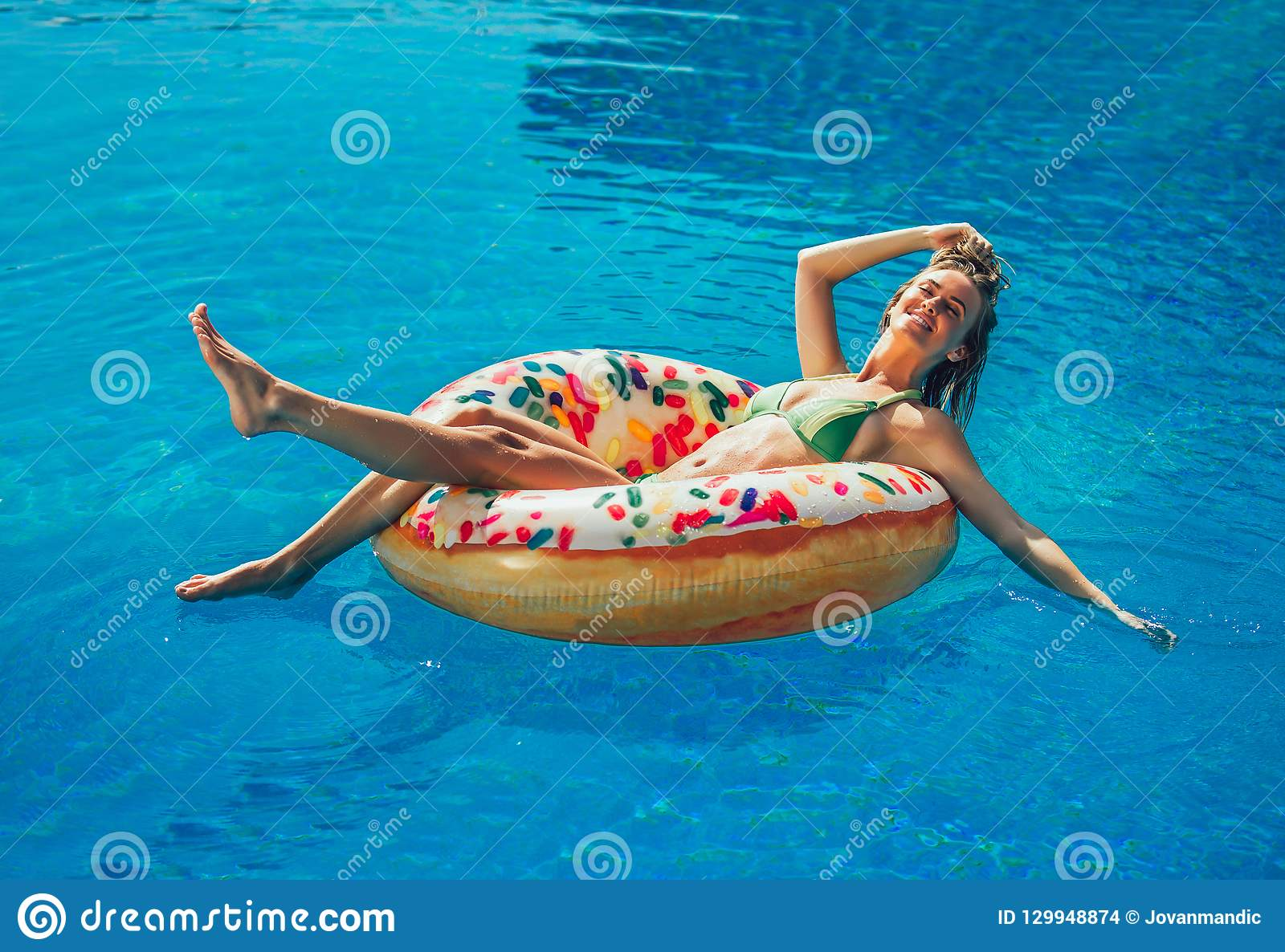Απόλαυση της suntan γυναίκας στο μπικίνι στο διογκώσιμο στρώμα στην πισίνα