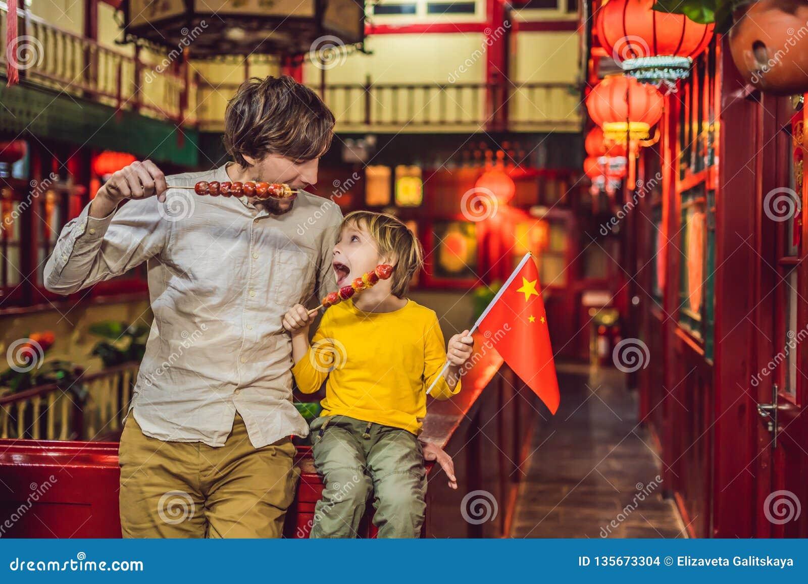 Απόλαυση των διακοπών στην Κίνα Ο ευτυχείς μπαμπάς και ο γιος τουριστών με έναν Κινέζο σημαιοστολίζουν και με τα γλασαρισμένα φρο