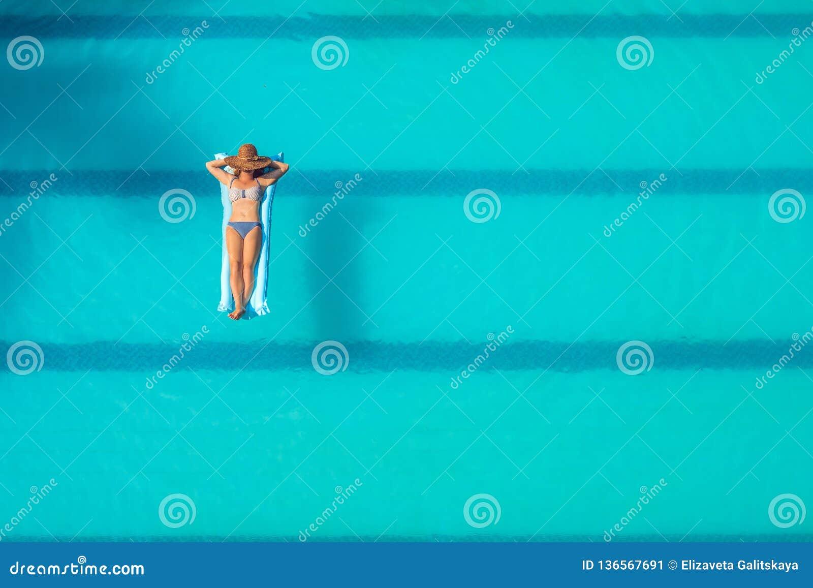 Απόλαυση suntan όμορφες νεολαίες γυναικών διακοπών λιμνών έννοιας Τοπ άποψη της λεπτής νέας γυναίκας στο μπικίνι στο μπλε στρώμα