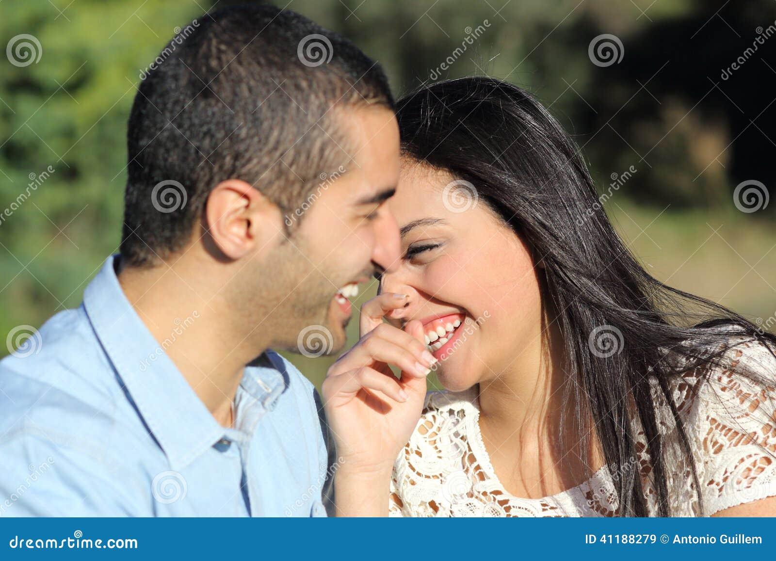 Αραβικοί περιστασιακοί άνδρας και γυναίκα ζευγών που φλερτάρουν και που γελούν ευτυχείς σε ένα πάρκο