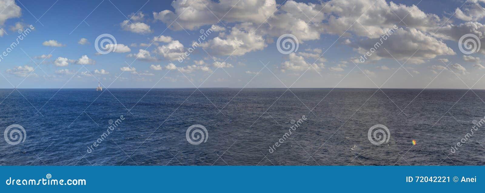 Αργά το απόγευμα φωτογραφία πανοράματος HDR της θάλασσας που εκτείνεται όλο τον τρόπο στον ορίζοντα και τον μπλε νεφελώδη ουρανό