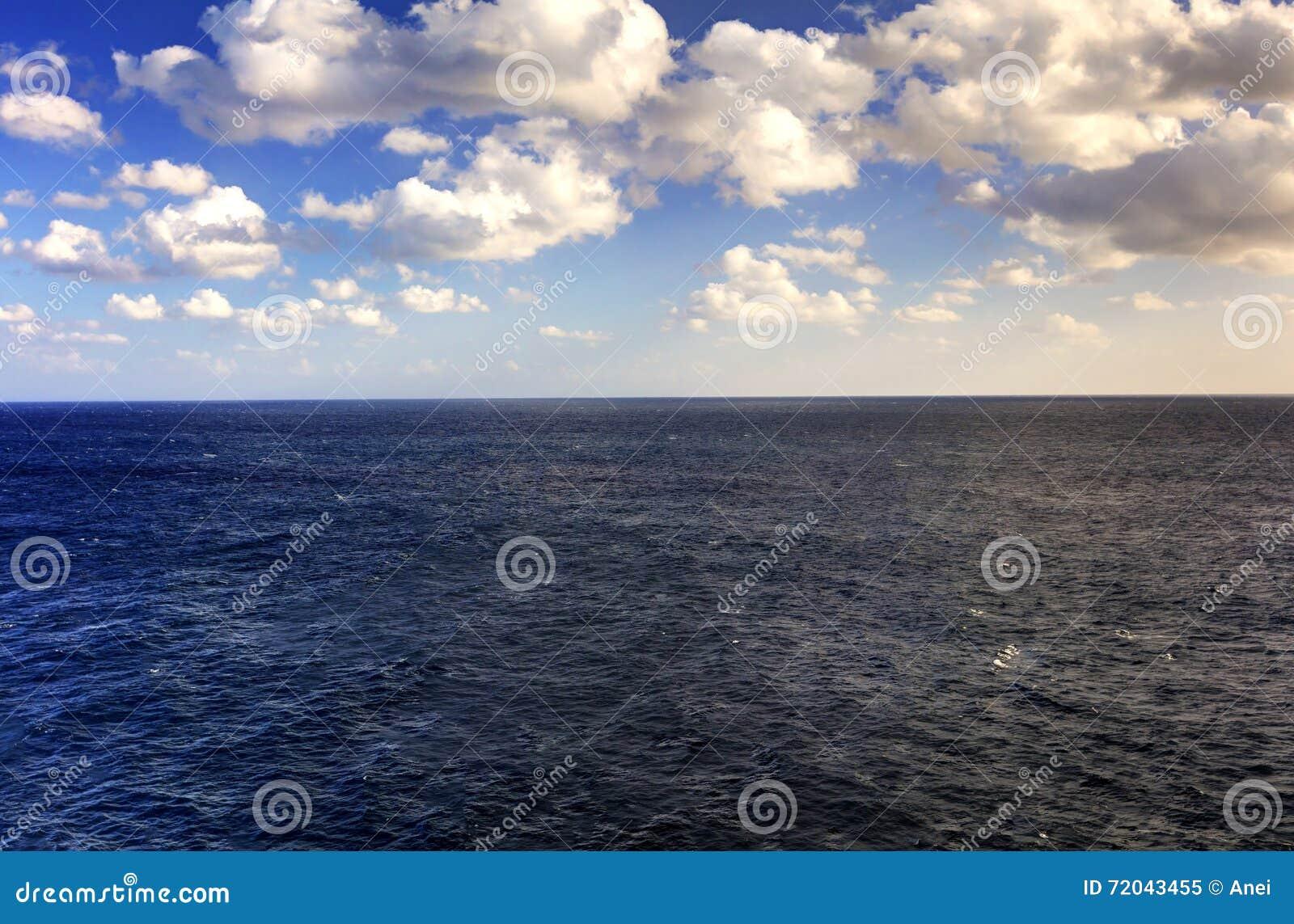 Αργά το απόγευμα φωτογραφία HDR της θάλασσας που εκτείνεται όλο τον τρόπο στον ορίζοντα και τον μπλε νεφελώδη ουρανό και το κόκκι