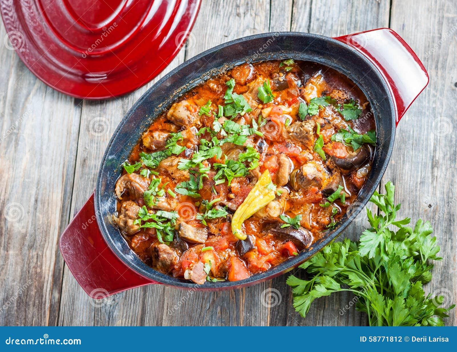 Αργό αρνί με τη μελιτζάνα και λαχανικά στο κόκκινο δοχείο