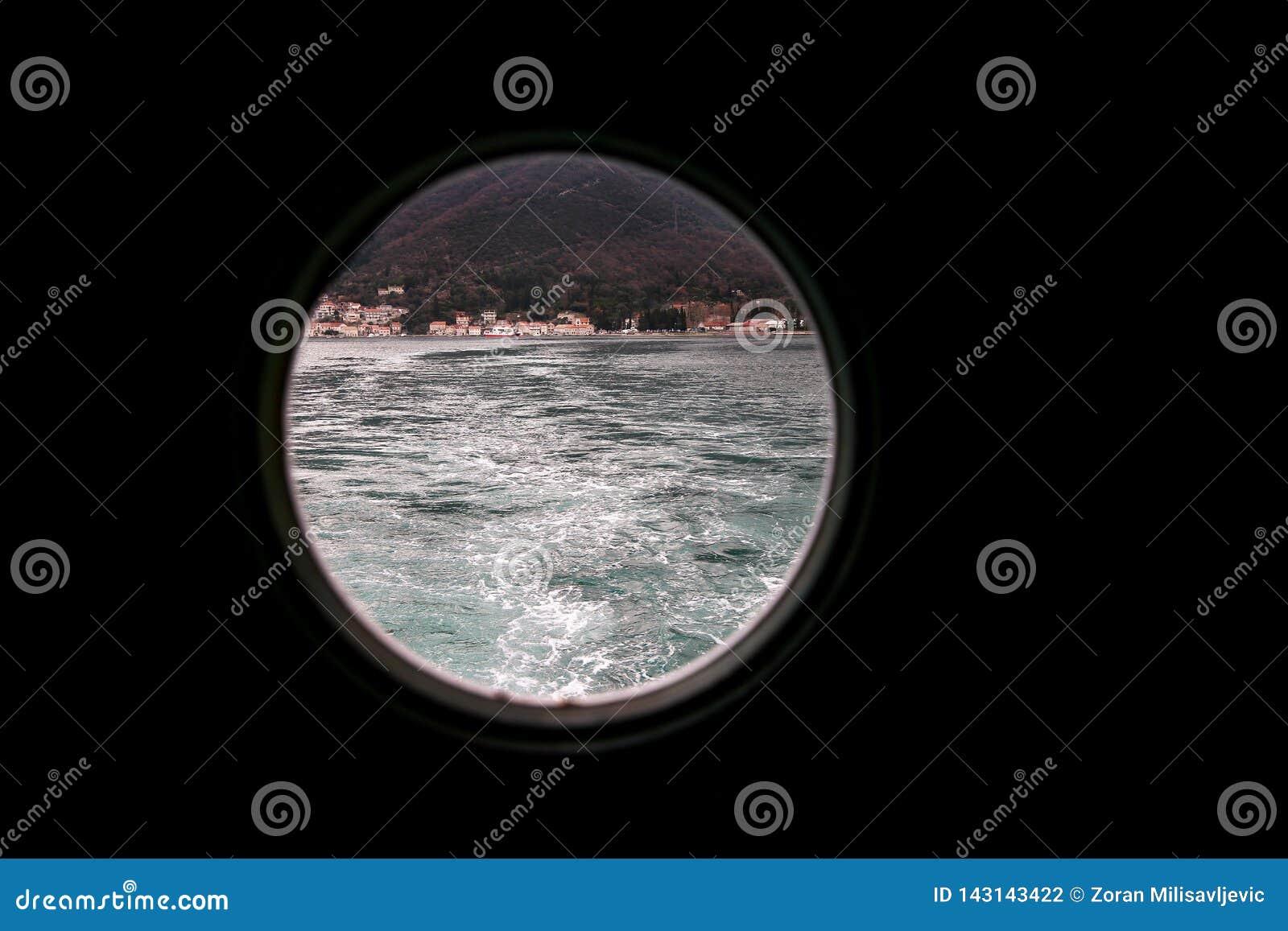 Αρθρωμένος γύρω από το παράθυρο, κάλυψη θύελλας στο σκάφος που κοιτάζει έξω στη Μεσόγειο Άποψη παραφωτίδων μέσω του παραθύρου στο