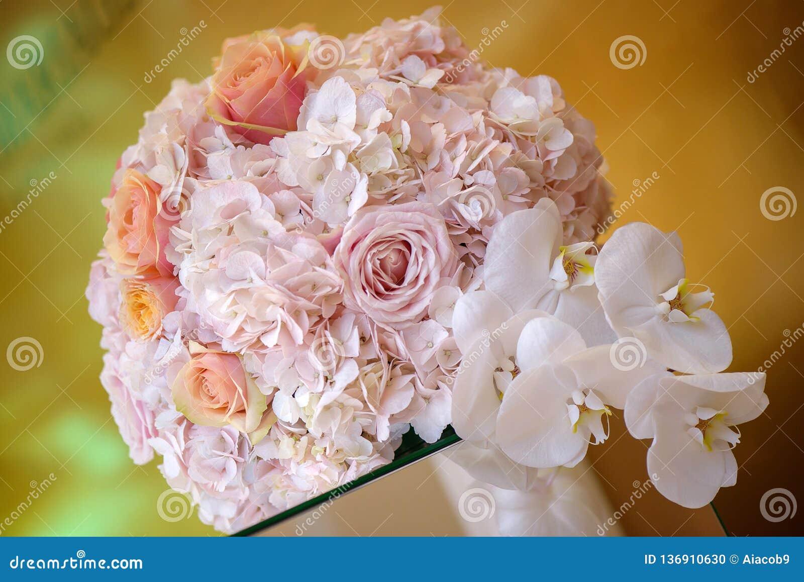 Αριστοκρατική floral ρύθμιση σε μια κρητιδογραφία γύρω από την ανθοδέσμη που χαρακτηρίζει τα ρόδινες τριαντάφυλλα και τις ορχιδέε