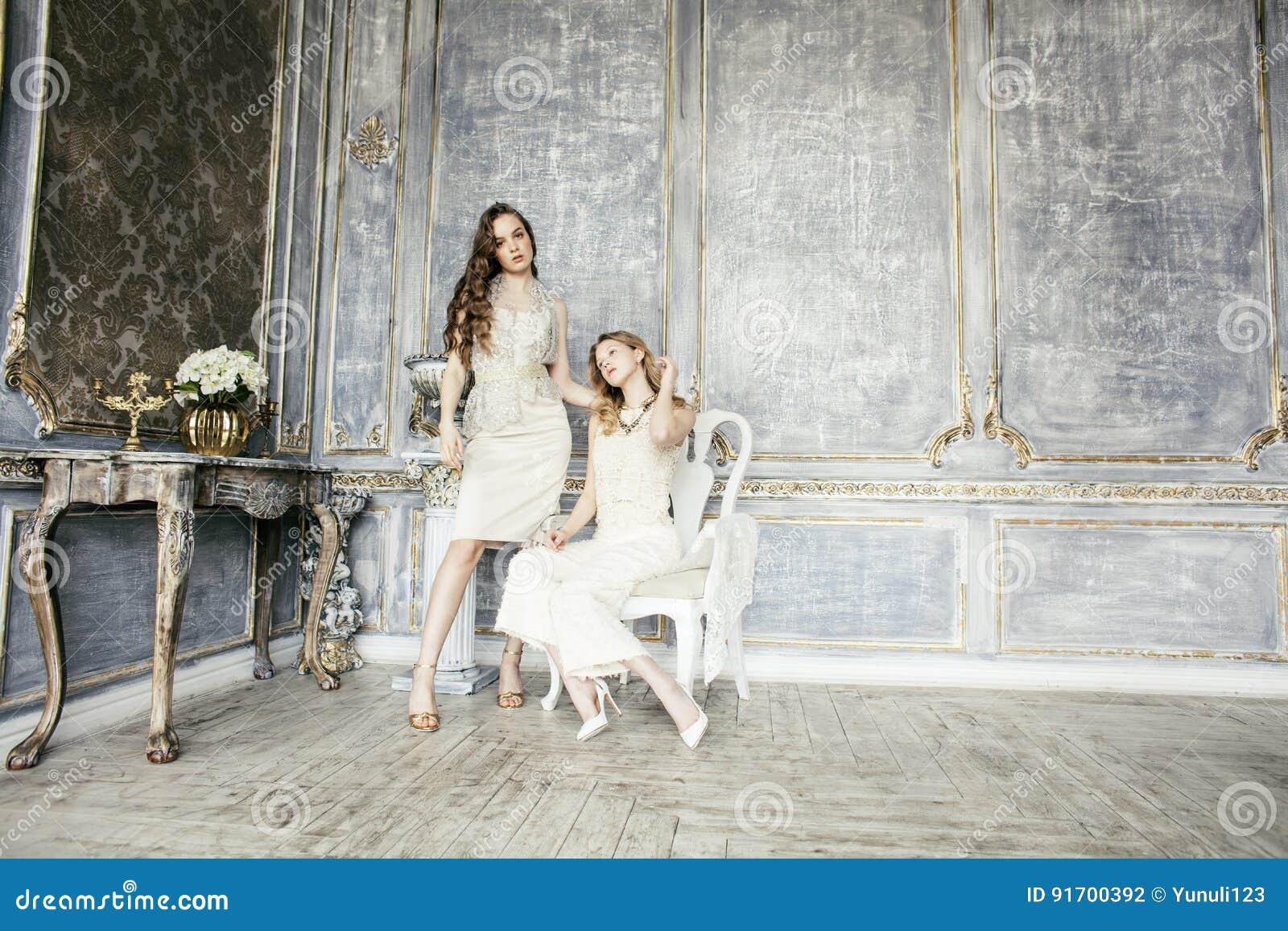 Αρκετά δίδυμο κορίτσι hairstyle αδελφών δύο ξανθό σγουρό στο εσωτερικό σπιτιών πολυτέλειας μαζί, πλούσια έννοια νέων